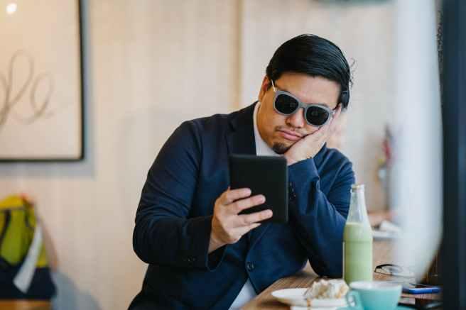 man wearing grey sunglasses holding black tablet